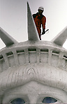 Snow sculptures worker looks down from a top of the Statue of Liberty snow sculpture in Odori Park. These are not traditional Frosty the Snowmen, but huge carved and chiseled Samurai Warriors, Buddhists gods, historical heroes of fairy tales and Walt Disney characters. Some stand as big as buildings. Chiseled out of tons of packed snow, the sculptures are the pride and job of the residents of Sapporo, Japan, who hosts the world famous Ice and Snow Sculpture Festival for five days in early February.Themes of the sculptures are picked from Kabuki stages, historical characters or fairy tales. (Jim Bryant Photo)........