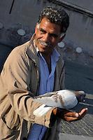Uomo da da mangiare ai piccioni.Man while gives the food to the pigeons...