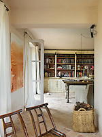 A large dresser housing a collection of books runs along the length of the end wall of the living/dining room