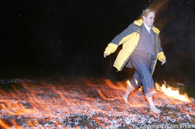 Share DeWees, Gig Harbor resident, walks across a bed of coals estimated to be 1200 degree Fahrenheit.  Jim Bryant Photo