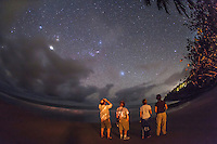 Stargazers having a look at the southern hemisphere sky, from a beach near Port Douglas, Queensland, Australia. Jupiter is the bright object in the clouds at left, Sirius is above the people, and Canopus is above the bushes at right. Orion is rising left of centre, on its side. This is taken looking east from a latitude of 16.5&deg; South.