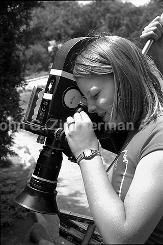 "Actress Jodie Foster, age 14, looks through eye piece of motion picture camera while appearing in the documentary film, ""Americans,"" Los Angeles, June, 1977. Photo by John G. Zimmerman. P94427-C05-F6A."