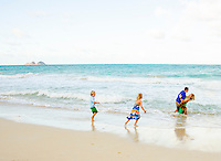 A family of four playing in the surf at Waimanalo Beach, O'ahu.