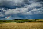 Idaho, Eastern, Teton Valley, Felt. Stormy skies and a partial rainbow over the farmlands of Eastern Idaho in late summer.