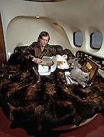 Playboy founder Hugh Hefner and cats aboard private lear jet. 1973. Photo by John G. Zimmerman