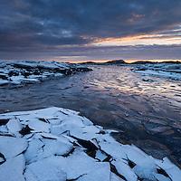 Frozen ice covers coastline in winter, near Nedredal, Vestvågøy, Lofoten Islands, Norway