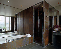 The contemporary bathroom is tiled with slate and has a walk-in shower in one corner