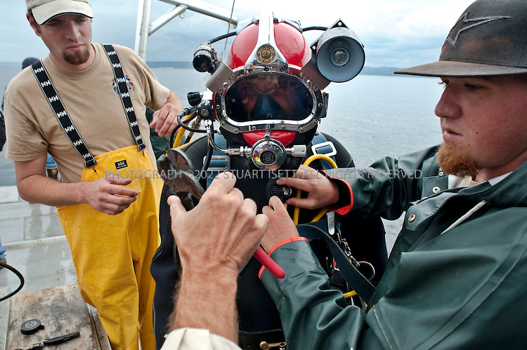 8/14/2009--Puget Sound, Seattle, WA, USA..Jeromy Meyer (center) prepares to dive to remove nets from Puget Sound. ..Right: Jake Johnston, left: Chris Melson - all divers with  Nisqually Aquatic Technologies...Jeff Choke, a member of the Nisqually Indian tribe in Washington State, and director of marketing for Nisqually Aquatic Technologies, a  diving company, has been hired using federal stimulus dollars to remove old nets in Puget Sound that destroy habitat and kill fish and other marine animals. The Nisqually indians are one of many tribes whose fishing has been affected by the big commercial fishing nets that came to deplete fish populations and damage the Sound....©2009 Stuart Isett. All rights reserved.