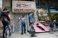 A migrant leaves the Athens office of the Greek Council for Refugees while another man is on hunger strike to get a status as a political refugee. The door of the office is painted with swastikas. According to UNHCR, 38,992 immigrants arrived in Greece in the first 10 months of 2010, whereas in 2009 the number was only 7,574.