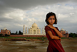 A young girl child who lives in the villages behind the world's most famous historical monument The Taj Mahal, watches intently and with certainty that the mounument behind her is the focus of attention and importance for the photographer. Photograph &copy; Santosh Verma