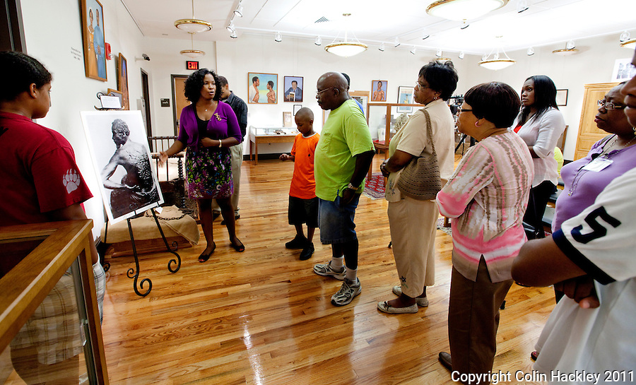 PAINFUL PAST: Tanisha Matthews, second from left, talks about the photo of a whip-scarred slave as she leads a tour for the Robinson family reunion through the Slavery in the Old South collection of The Black Archives in Tallahassee..COLIN HACKLEY PHOTO