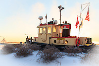 &quot;At the Light of Dawn&quot;<br /> The rising sun radiates the inner light of the tugboat as sea smoke risese in the distance.