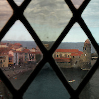 Eglise Notre Dame des Anges, Collioure, France, seen through a window in the keep of the Chateau Royal. The bell tower was converted from a medieval lighthouse and the Mediterranean Gothic style nave was built in 1684. The dome was added to the bell tower in 1810. Picture by Manuel Cohen.
