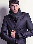 Fashion portrait of a young man wearing a black blazer and a scarf isolated on white background