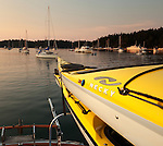 Looking down the length of a kayak mounted on the rear of a small boat, many sailboats are seen anchored in a small harbor along the coast of British Columbia.