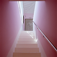 View up the staircase with white wooden steps and pink walls