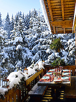The table on this sheltered terrrace is laid for al fresco dining and has unrestricted views of the snow-covered forest which surrounds the chalet