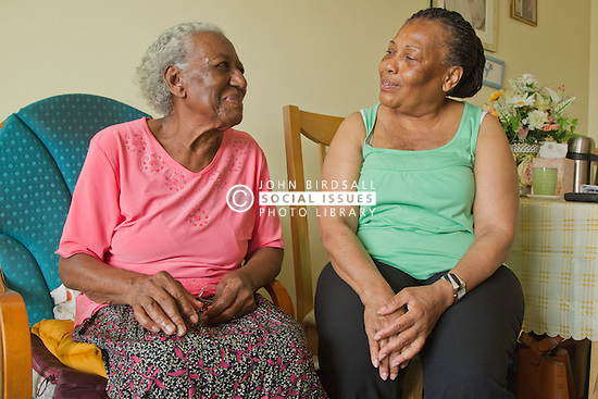 Carer and elderly visually impaired woman chatting
