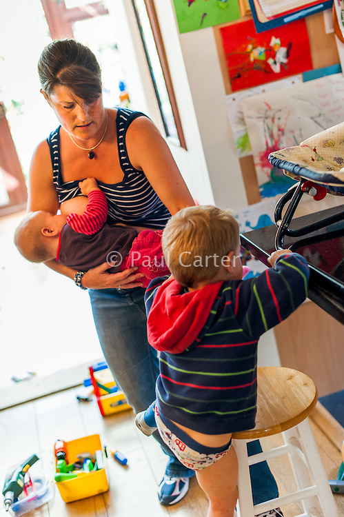 A mother breastfeeds her baby while helping her older child sit up at the breakfast bar for his meal.<br /> <br /> 30 August 2012<br /> Hampshire, England, UK