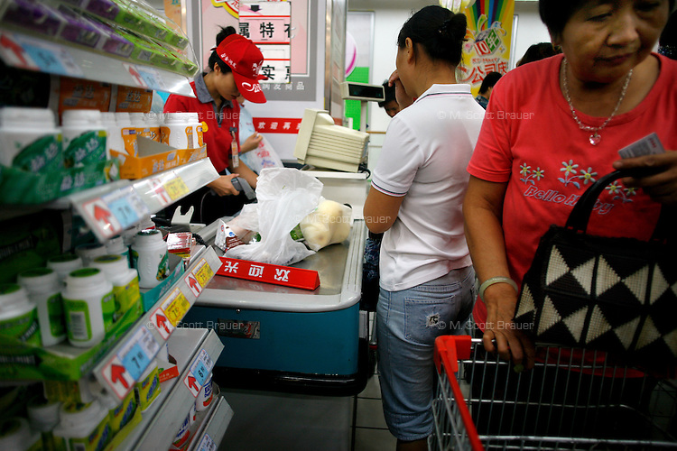 People wait in the checkout line at the RT Mart supermarket in Nanjing, China.