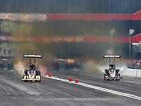 Jun 20, 2015; Bristol, TN, USA; NHRA top fuel driver Leah Pritchett (left) races alongside Terry McMillen during qualifying for the Thunder Valley Nationals at Bristol Dragway. Mandatory Credit: Mark J. Rebilas-