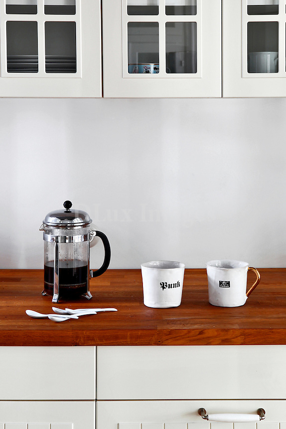 coffee maker and mugs on wooden countertop