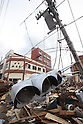 March 17, 2011, Kesennuma CIty, Iwate Prefecture, Japan - Power lines and a traffic signal hang tilted over the tsunami debris clogging Kesennuma, Iwate Prefecture, Japan, inthe aftermath of the 2011 Tohoku-Kanto Natural Disaster. (Photo by Yousuke Miyamori/AFLO)