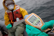 Crew from the Greenpeace ship Rainbow Warrior collect sea water samples to monitor radiation contamination levels, as the ship sails up the eastern coast of Japan, in the vicinity of Fukushima, in Japan, Tuesday 3rd May 2011..Collecting a sample of seawater at coordinates 37' 02.246 North, 141' 24.658 East.