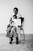 A Sri Lankan woman (name withheld on request) poses for a photo with her child and the CHDR- Child Health Development Record Card (immunization/vaccination card) in the Ministry of Health office in Tharmapuram Village in Kilonochchi, Sri Lanka.  Photo: Sanjit Das/Panos