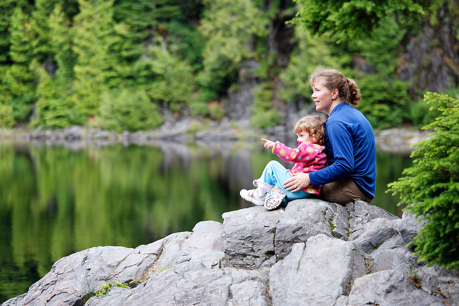 Little girl and mother hikers sitting on rock pointing and looking at lake, Boardman Lake, Cascade Mountains, Washington, USA