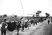 This picture, captured from the Japanese, shows American prisoners using improvised litters to carry those of their comrades who, from the lack of food or water on the march from Bataan, fell along the road.  Philippines, May 1942. (OWI)<br /> Exact Date Shot Unknown<br /> NARA FILE #:  208-AA-288BB-2<br /> WAR &amp; CONFLICT BOOK #:  1145