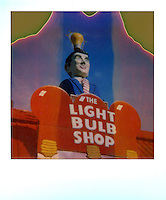 "In this instant-film image shot on expired Polaroid 600 film, a light bulbs-only specialty store is topped by a smartly dressed man with a classic ""IDEA"" light bulb over his head - Stock Image."