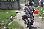 A child sleeps while his father drives a motorcycle in Lamreh, in Indonesia's Aceh province.