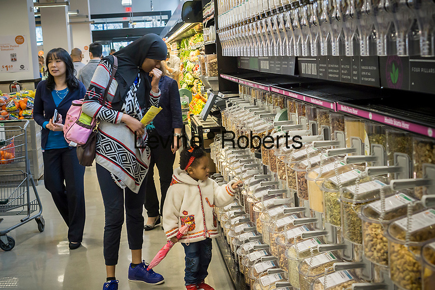 Shoppers choose bulk grains and nuts in the new Whole Foods Market in Newark, NJ on opening day Wednesday, March 1, 2017. The store is the chain's 17th store to open in New Jersey. The 29,000 square foot store located in the redeveloped former Hahne & Co. department store building is seen as a harbinger of the revitalization of Newark which never fully recovered from the riots in the 1960's.  (© Richard B. Levine)