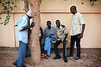 A small group of men settled down in front of the ' PMU club (HORSE-RACING BETTING), shielded from the sun but also from the indiscreet ears. Paul Kissou, a day guard, listens carefully the tactics of one of them to obtain the good combinations.