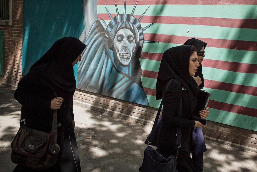 Iranian pass the anti America murals at the ex U.S Embassy (now called Den of Espionage) in Tehran.