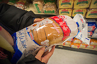 A shopper buys a loaf of Bimbo brand white bread in a supermarket New York on Saturday, December 22, 2012. The Mexican conglomerate Bimbo, which already owns Sara Lee, Entenmann's and other bakeries is considering purchasing Hostess Bakeries. (© Richard B. Levine)