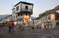 The Qafe or Neck of the Bazaar, a busy intersection of 5 streets that forms the heart of the old town of Gjirokastra, Southern Albania, with the Kalaja e Gjirokastres or Gjirokastra Castle on the right. Most of the Ottoman houses date from the 17th and 18th centuries. Gjirokastra was settled by the Greek Chaonians, the Romans and Byzantines before becoming an Ottoman city in 1417. Its old town was listed as a UNESCO World Heritage Site in 2005. Picture by Manuel Cohen