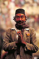 Smiling middle-aged man in threadbare suit gives Namaste greeting; scarf; flowers in lapel. Kathmandu, Nepal.