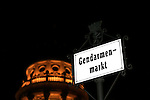 Signpost Gendarmenmarkt in Berlin, capital of  Germany, with French cathedral by night