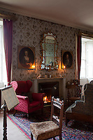 The sitting room, lit only by the warm glow of fire and candlelight, illuminating the gilt frames of the portraits