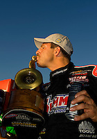 Sept. 19, 2010; Concord, NC, USA; NHRA pro stock driver Greg Anderson kisses the trophy after winning the O'Reilly Auto Parts NHRA Nationals at zMax Dragway. Mandatory Credit: Mark J. Rebilas-
