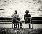 A man and a woman, both sitting on the end of 2 separte benches, staring into the ocean