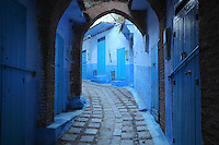 Narrow sloping street with overhead arches, painted blue, in the medina or old town of Chefchaouen in the Rif mountains of North West Morocco. Chefchaouen was founded in 1471 by Moulay Ali Ben Moussa Ben Rashid El Alami to house the muslims expelled from Andalusia. It is famous for its blue painted houses, originated by the Jewish community, and is listed by UNESCO under the Intangible Cultural Heritage of Humanity. Picture by Manuel Cohen
