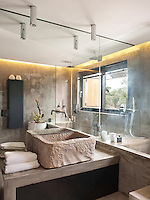 A contemporary bathroom with polished concrete walls and built-in features and a rough-hewn stone basin
