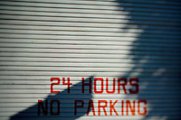 24 hours no parking painted on a garage door in San Francisco