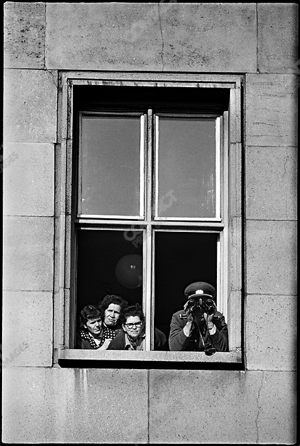 East Germans looking into West Berlin from a window near the construction of the Berlin Wall. Viewed from West Berlin, Germany, November, 1961