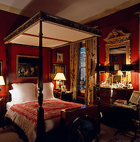 A four-poster bed with a carved top dominates this dark red bedroom which is filled with objects