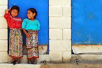 portrait of 2 young girls from guatemala in colorful traditional cloths in front of blue door, Cunen, Nebaj, Guatemala Few years ago photographers Anthony Asael and Stepahnie Rabemiafara dreamed a dream that seemed quite imposible: to visit every country of the World promoting arts and tolerance among children and, of course, taking photographs of them. With little money and resources but an impressing will, the duo got an astonishing goal. In four years they visited 300 schools in 192 countries where kids participating of the project created 18,000 pieces of artwork. <br />