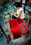 A woman spinning silk the traditional Lao way for weaving at Carol Cassidy Lao Textiles, Vientiane, Laos.